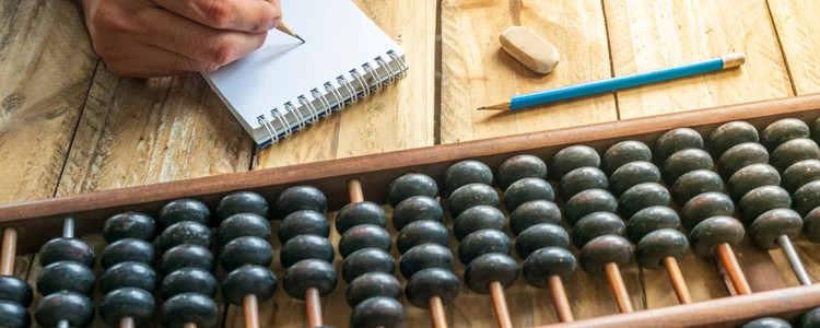 person with pencil and notebook counting on abacus