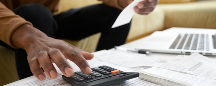 man with paperwork using calculator