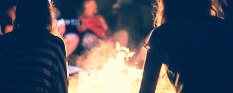 People sitting around a bright bonfire at night