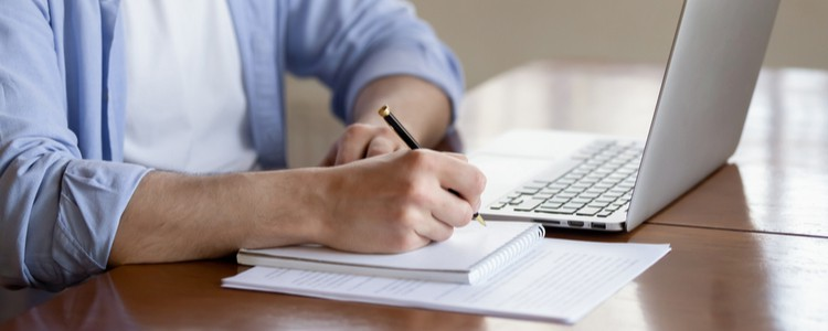 male student making notes while watching laptop screen
